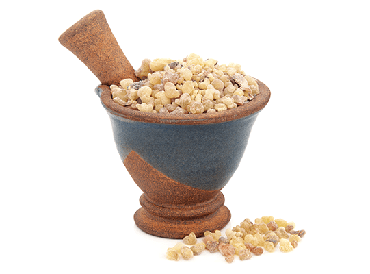 Frankincense displayed in a beautiful stonework mortar and pestle, on a white background.