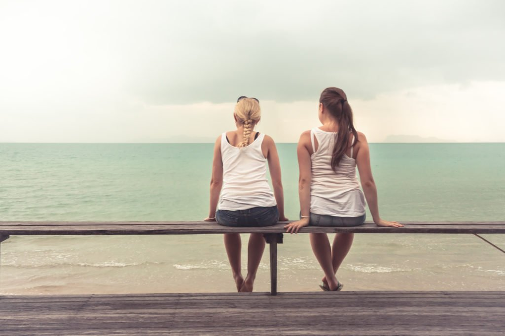 Two women viewed from behind. They are wearing jeans and t-shirts, and sitting casually on a bench overlooking the beach.